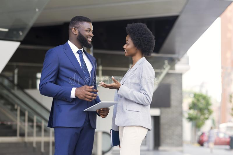 Compañeros de trabajo africanos atractivos que tienen charla agradable junto fotografía de archivo