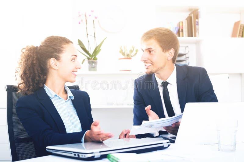 Compañeros de trabajo alegres del hombre joven y de la mujer que hablan en oficina firme imagen de archivo