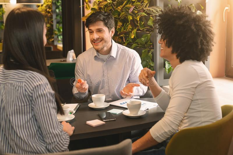 Compañeros de trabajo alegres que discuten proyectos del negocio durante tiempo del almuerzo imagenes de archivo