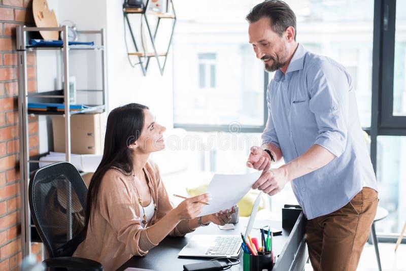 Compañeros de trabajo alegres que tienen conversación necesaria imagenes de archivo