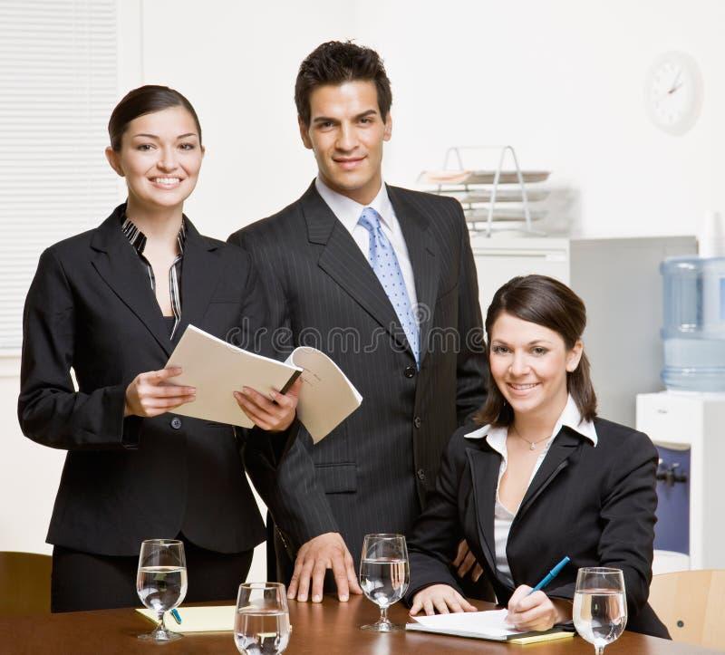 Compañeros de trabajo con papeleo en la sala de conferencias fotos de archivo