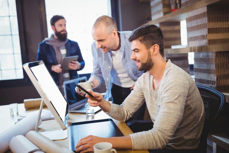 Compañeros de trabajo creativos masculinos que discuten sobre el ordenador fotos de archivo libres de regalías
