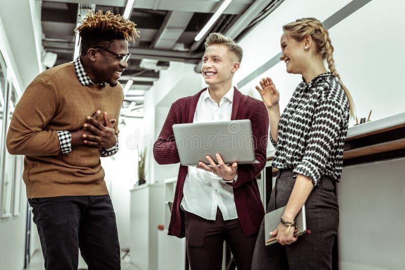 Compañeros de trabajo elegantes positivos que ríen hacia fuera ruidosamente mientras que se une foto de archivo libre de regalías
