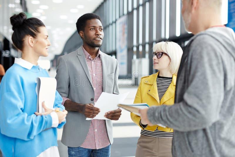 Compañeros de trabajo en la reunión en pasillo foto de archivo