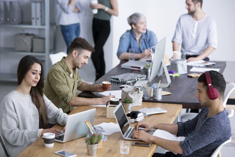 Compañeros de trabajo en oficina moderna imagen de archivo