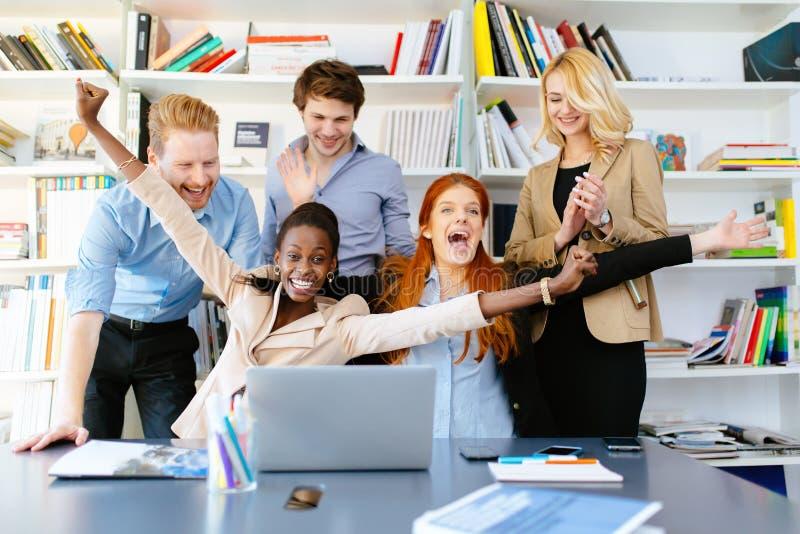 Compañeros de trabajo felices del negocio que celebran imagen de archivo