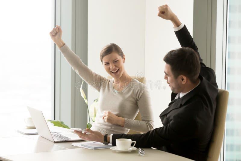 Compañeros de trabajo felices de la oficina que disfrutan de crecimiento del negocio imagenes de archivo
