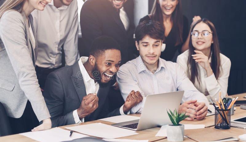 Compañeros de trabajo felices que celebran el inicio acertado que mira el ordenador portátil foto de archivo