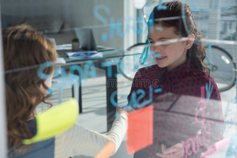 Compañeros de trabajo femeninos que discuten por la ventana vista a través del vidrio fotografía de archivo