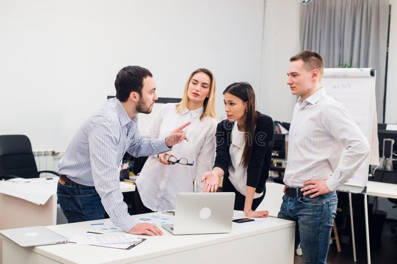 Compañeros de trabajo jovenes del grupo que toman grandes decisiones económicas Oficina moderna creativa de Team Discussion Corpo imágenes de archivo libres de regalías