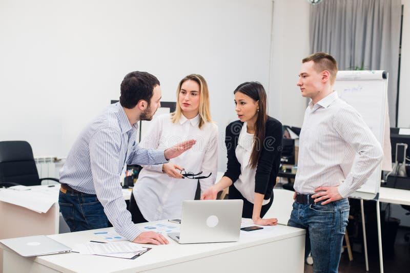 Compañeros de trabajo jovenes del grupo que toman grandes decisiones económicas Oficina moderna creativa de Team Discussion Corpo fotos de archivo