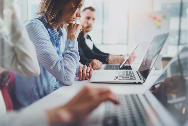 Compañeros de trabajo jovenes que trabajan con los ordenadores móviles en la sala de reunión soleada horizontal fotos de archivo libres de regalías