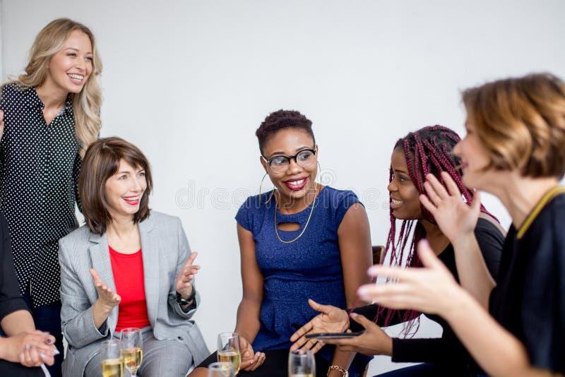 Compañeros de trabajo de las hembras que celebran arranque acertado de un nuevo proyecto imágenes de archivo libres de regalías