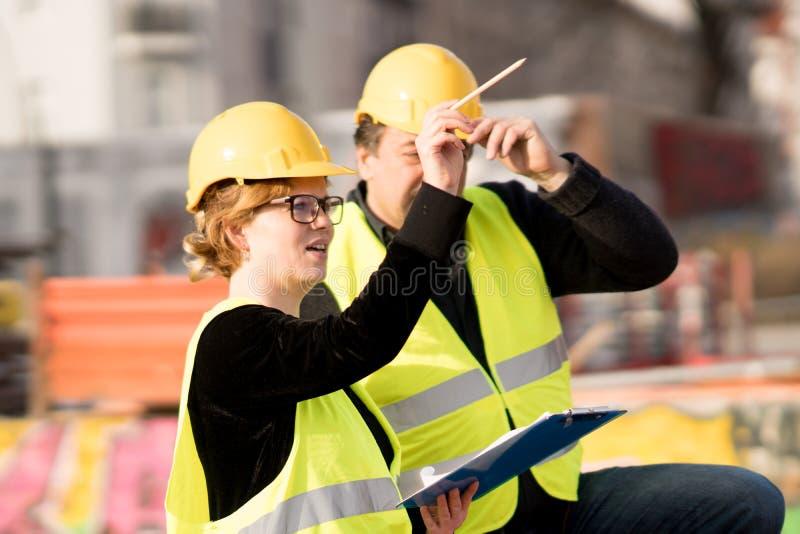 Compañeros de trabajo masculinos y femeninos en emplazamiento de la obra imagen de archivo libre de regalías