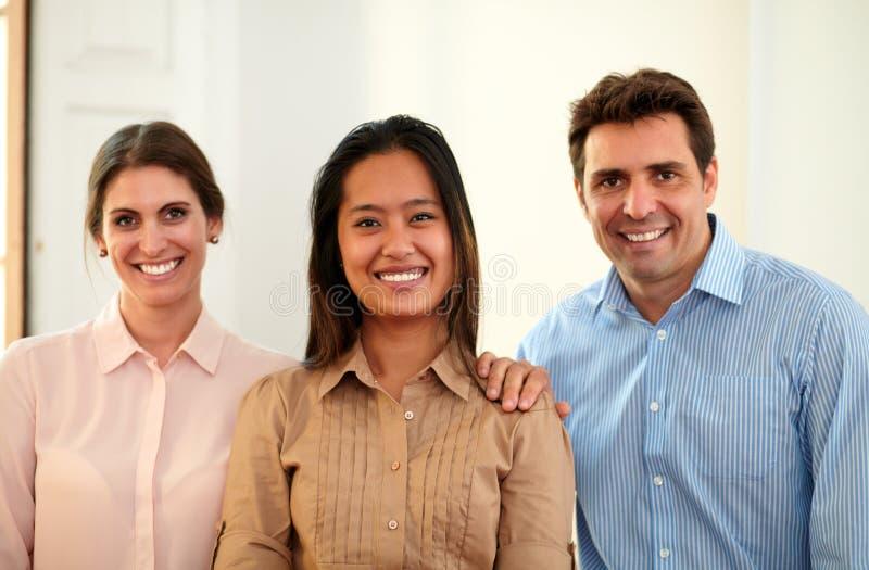 Compañeros de trabajo masculinos y femeninos que sonríen en usted foto de archivo
