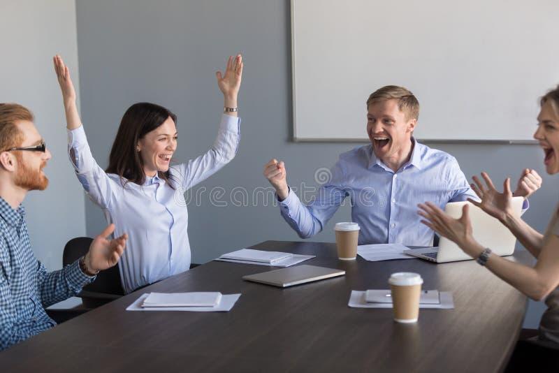 Compañeros de trabajo motivados emocionados del equipo que celebran busine increíble fotos de archivo libres de regalías