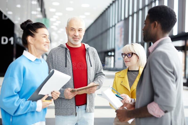 Compañeros de trabajo multirraciales en pasillo grande foto de archivo libre de regalías