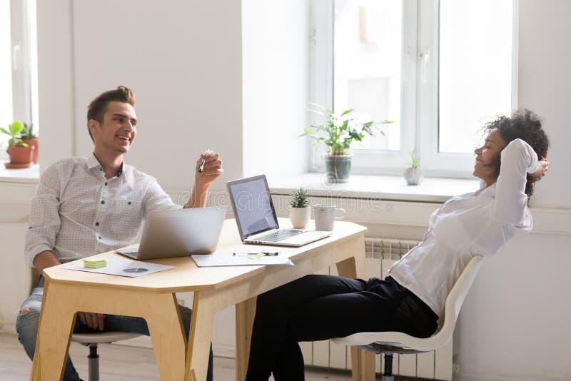 Compañeros de trabajo multirraciales milenarios que charlan y que ríen tomando el Br fotos de archivo