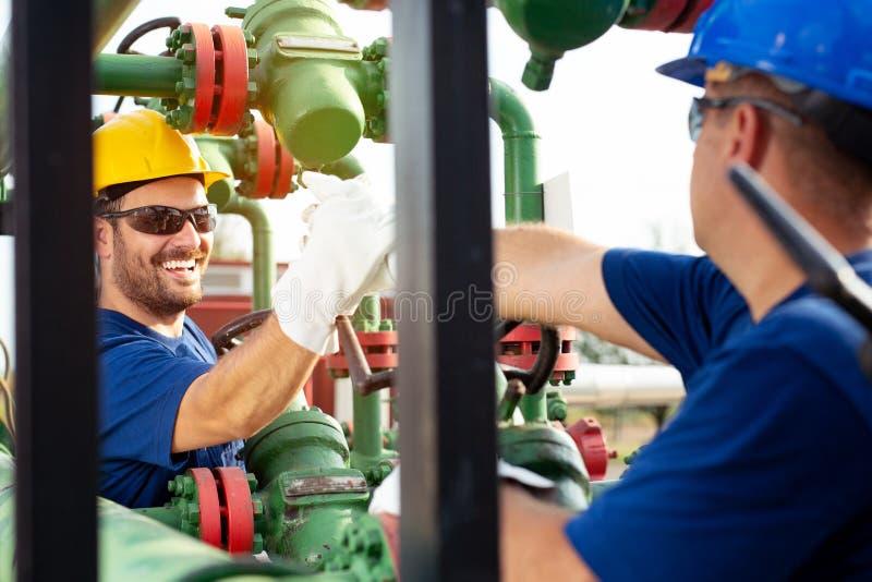 Compañeros de trabajo petroquímicos que trabajan en la planta de refinería fotografía de archivo