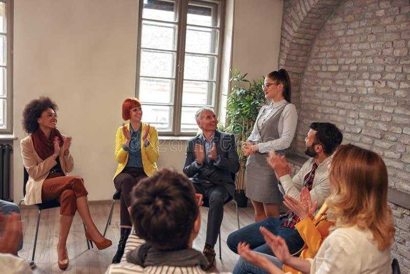Compañeros de trabajo que aplauden a la mujer en la reunión de grupo fotos de archivo libres de regalías