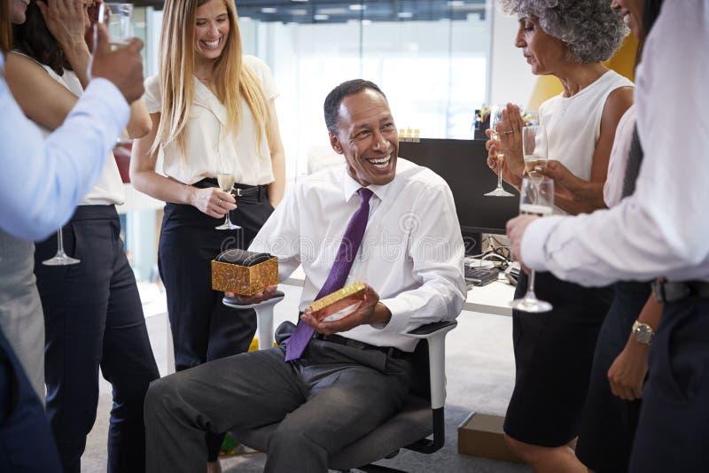 Compañeros de trabajo que celebran un retiro del ½ s del ¿del colleagueï en la oficina foto de archivo