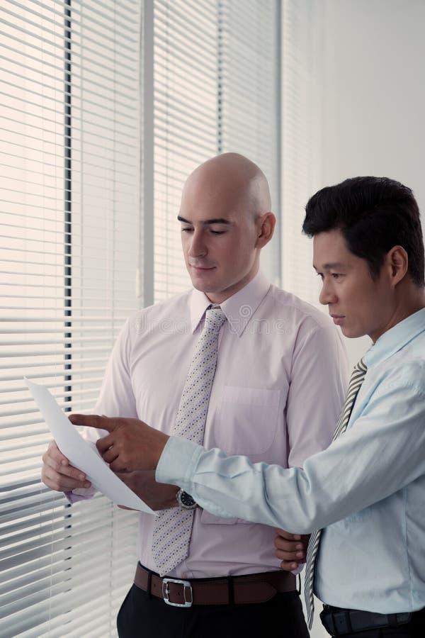 Compañeros de trabajo que discuten datos imagen de archivo libre de regalías