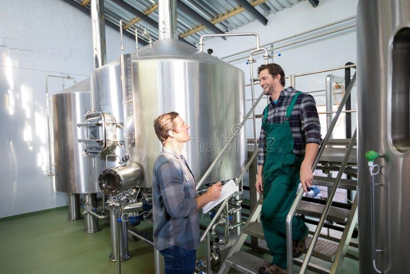 Compañeros de trabajo que discuten mientras que hace una pausa los tanques de almacenamiento en la cervecería fotos de archivo libres de regalías