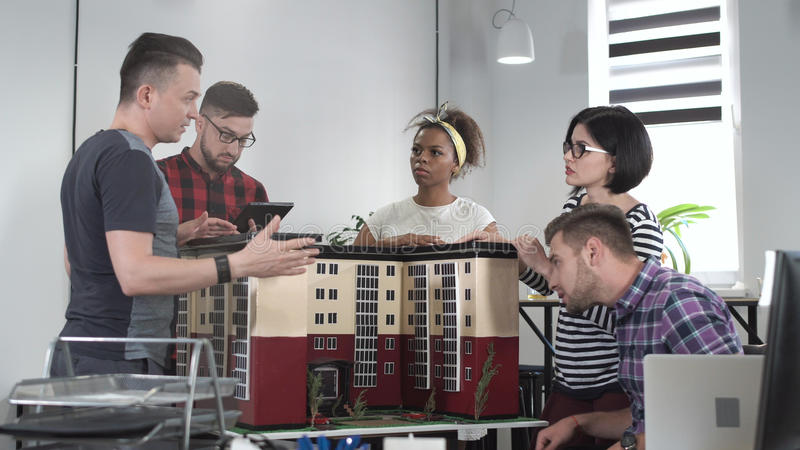 Compañeros de trabajo que discuten por la miniatura del edificio fotos de archivo