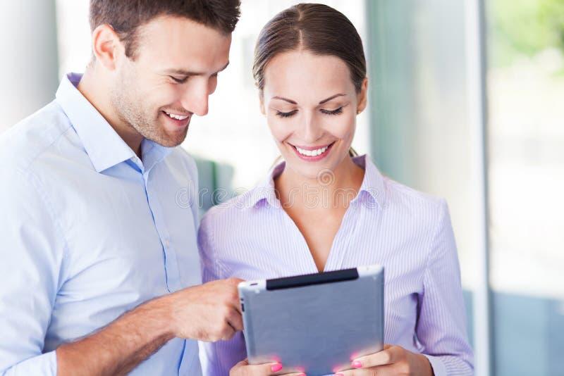 Compañeros de trabajo que miran la tableta digital fotografía de archivo
