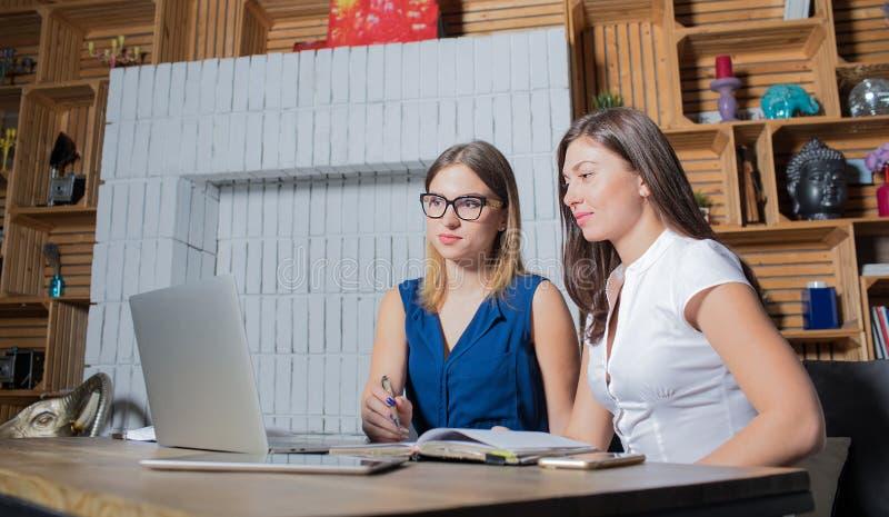 Compañeros de trabajo que tienen reunión, funcionamiento junto en el ordenador portátil, información de la lectura sobre página w foto de archivo libre de regalías