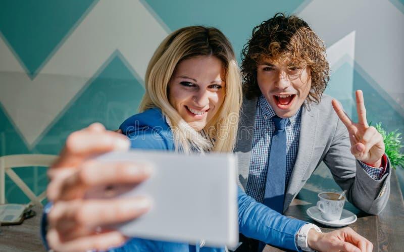 Compañeros de trabajo que toman un selfie que celebra éxito imagen de archivo