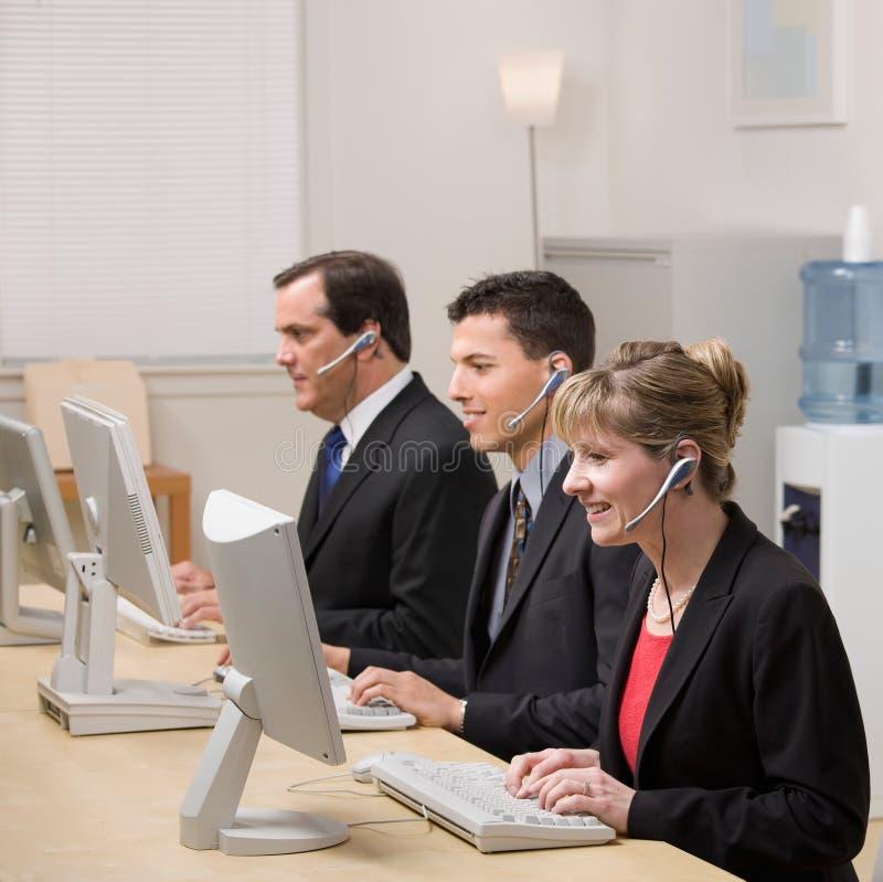 Compañeros de trabajo que trabajan en los ordenadores en centro de atención telefónica fotos de archivo libres de regalías
