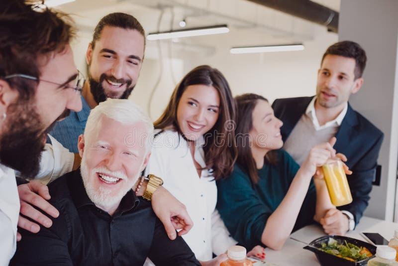 Compañeros de trabajo sonrientes que almuerzan en la cafetería imagen de archivo