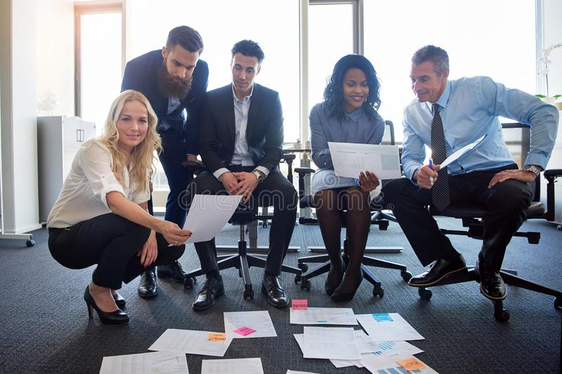 Compañeros de trabajo sonrientes que discuten el papeleo junto en una oficina moderna fotos de archivo libres de regalías