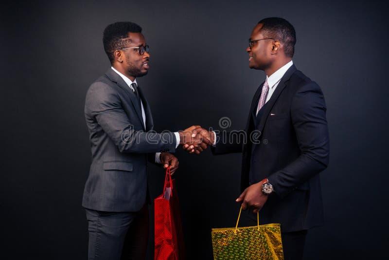 Compañeros hombres de negocios afroamericanos sosteniendo bolsas de compras con fondo negro en el estudio. Venta negra de viernes imagen de archivo libre de regalías