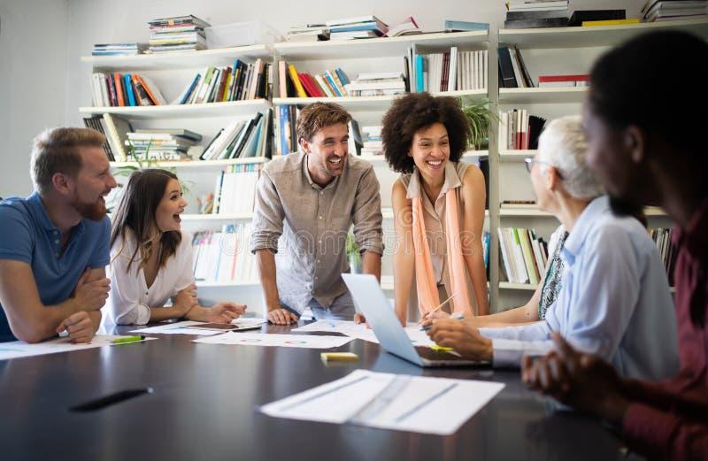 Compa?eros de trabajo alegres en oficina durante la reuni?n de compa??a foto de archivo libre de regalías
