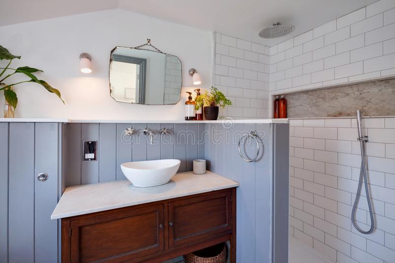 Compact contemporary wet room. Contemporary compact wet room with traditional twist including washstand, basin with fawcet above, marble top, wood panelled and royalty free stock image