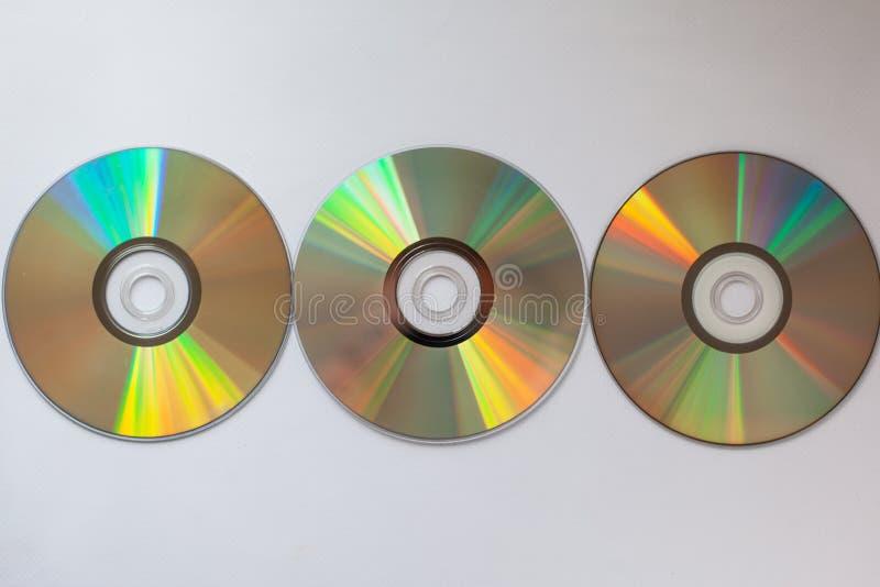 3 compact-disc del Cd con los conductores del ordenador en fila en un fondo blanco imagenes de archivo