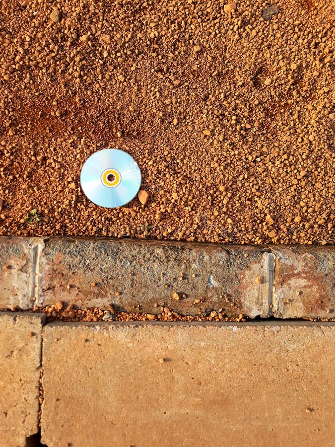 Compact disc was broken on brown soil and cement drain grates with abstract background. N stock photo