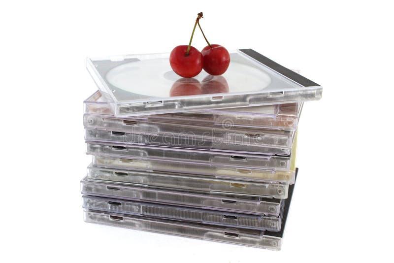 Compact-discs in pakken met twee kersen op bovenkant, close-up stock afbeeldingen