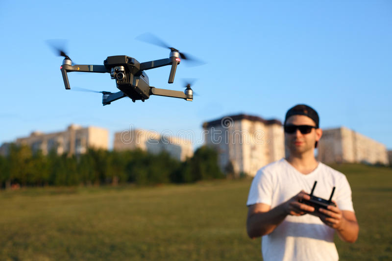 Compact drone hovers in front of man with remote controller in his hands. Quadcopter flies near pilot. Guy taking aerial. Photos and videos royalty free stock photography
