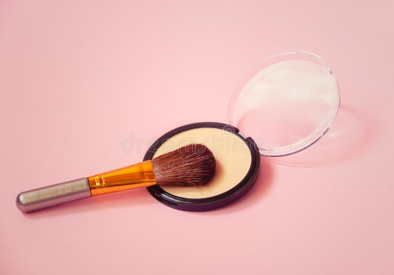 Compact face powder and makeup brush on pink background. Selective focus royalty free stock photos