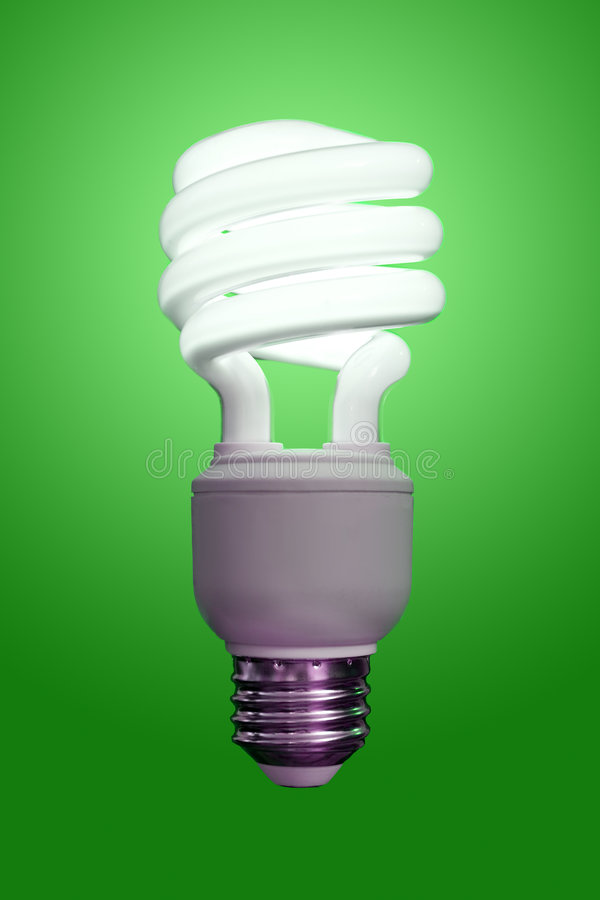 Compact Fluorescent Bulb. Close up of a compact fluorescent light bulb, turned on with a green gradient behind stock image