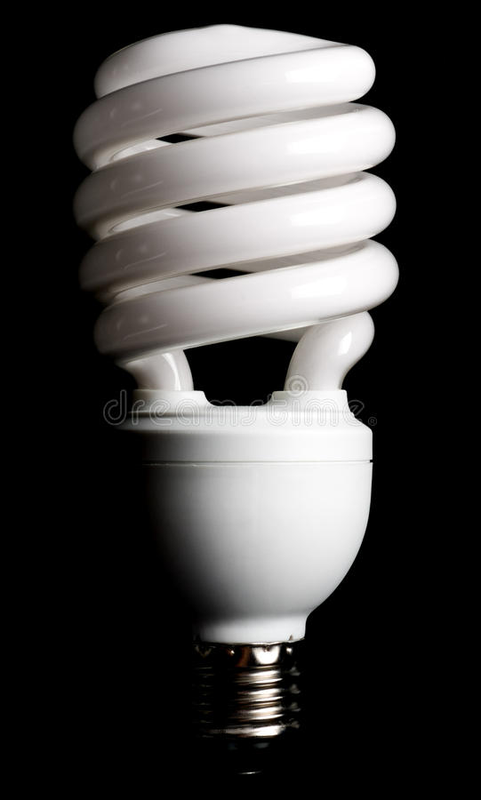 Compact fluorescent light bulb. Isolated on black background stock photography