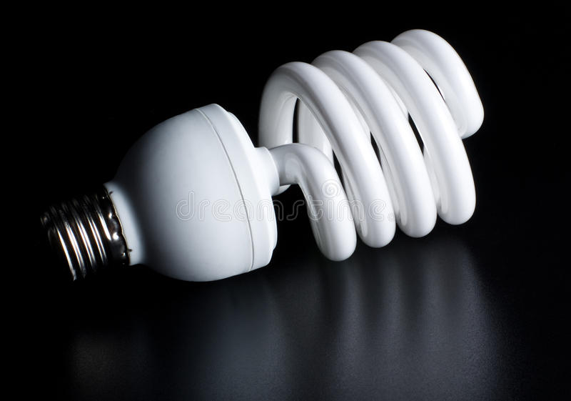 Compact fluorescent light bulb. Isolated on black royalty free stock photo