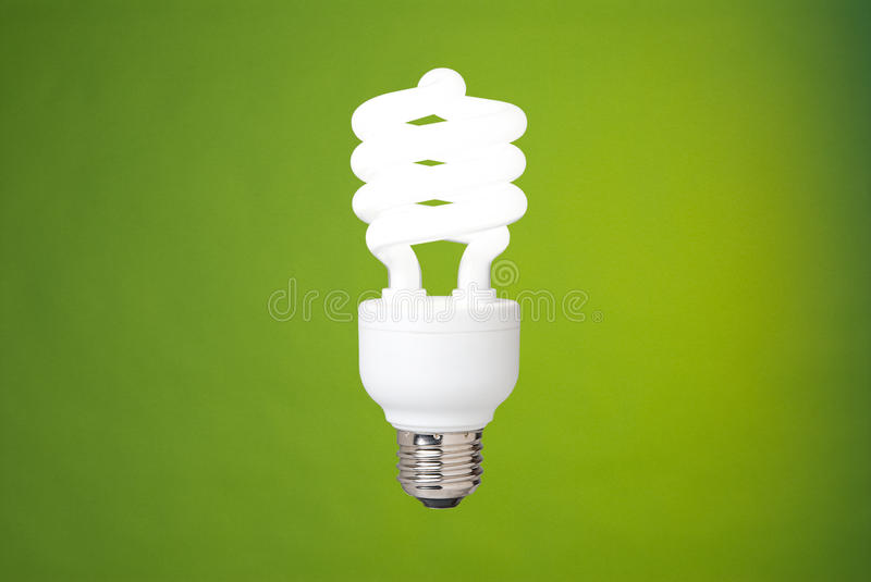 Compact fluorescent light bulb. A compact fluorescent light bulb against a green background royalty free stock images