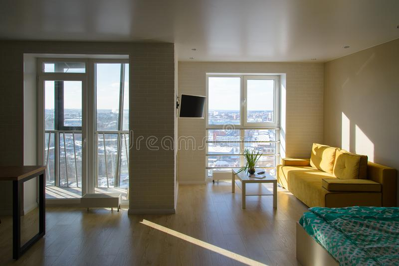 Compact modern cozy apartment interior, living room with yellow sofa, white coffee table and tv on wall, big windows and. Panoramic view from balcony royalty free stock photo