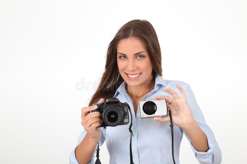 Compact or reflex?. Young woman comparing digital compact and reflex cameras stock photo