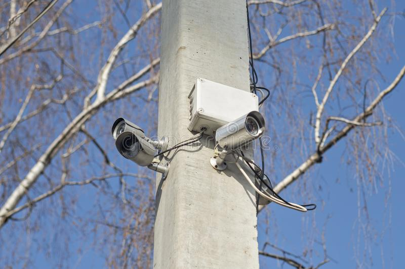 Compact video surveillance cameras on support post in public areas on blue sky. Security cameras on a pole stock photo