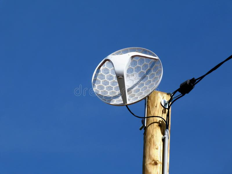 compact white dish telecommunication receiver on timber pole stock image